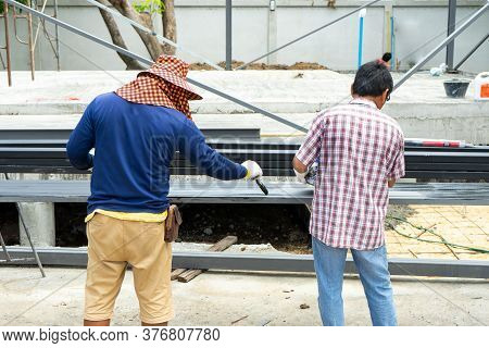 Back Portrait Of Workmen Painting The Black Colour On The Surface Of Steel Bars At The Construction