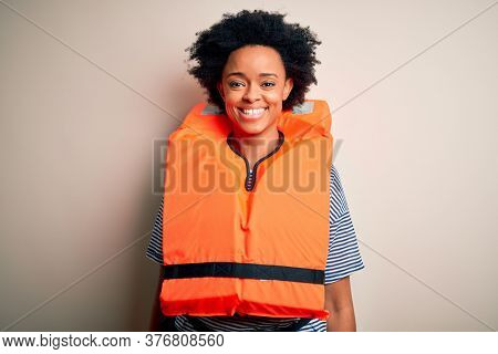 Young African American afro woman with curly hair wearing orange protection lifejacket with a happy and cool smile on face. Lucky person.
