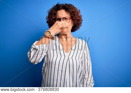 Middle age beautiful curly hair woman wearing casual striped shirt over isolated background smelling something stinky and disgusting, intolerable smell, holding breath with fingers on nose. Bad smell