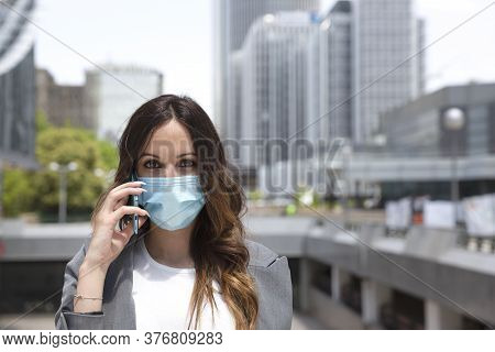 Close-up Of Young Entrepreneurial Woman Talking Through Her Smartphone Outside A Business Area. She