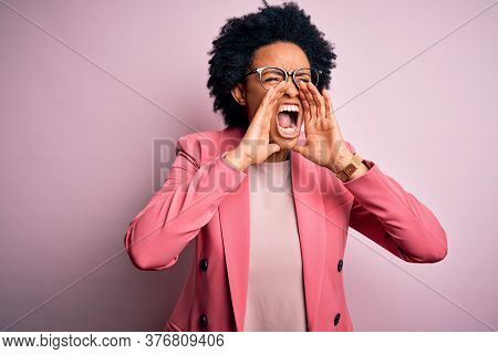 Young beautiful African American afro businesswoman with curly hair wearing pink jacket Shouting angry out loud with hands over mouth