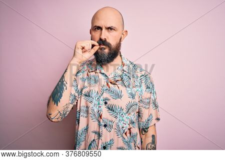 Handsome bald man with beard and tattoo wearing casual floral shirt over pink background mouth and lips shut as zip with fingers. Secret and silent, taboo talking