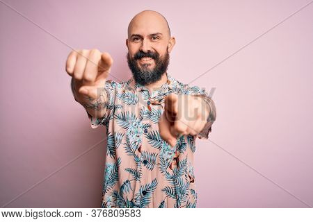 Handsome bald man with beard and tattoo wearing casual floral shirt over pink background pointing to you and the camera with fingers, smiling positive and cheerful