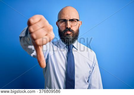Handsome business bald man with beard wearing elegant tie and glasses over blue background looking unhappy and angry showing rejection and negative with thumbs down gesture. Bad expression.