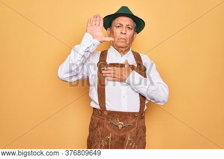 Senior grey-haired man wearing german traditional octoberfest suit over yellow background Swearing with hand on chest and open palm, making a loyalty promise oath