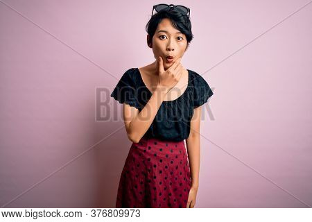 Young beautiful asian girl wearing casual dress standing over isolated pink background Looking fascinated with disbelief, surprise and amazed expression with hands on chin