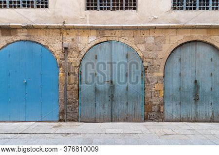 Row Of Closed Three Blue Weathered Wooden Arched Doors In Stone Bricks Wall, Located In Old Abandone