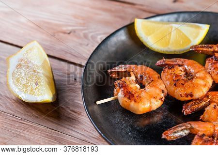 Appetizing Fried Shrimp On A Skewer In A Black Plate On A Wooden Surface Among Lemon And Seasonings.