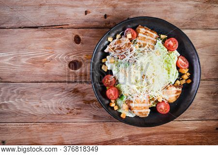 Appetizing Caesar Salad With Chicken In A Black Plate On A Wooden Table. The Concept Of Healthy Food