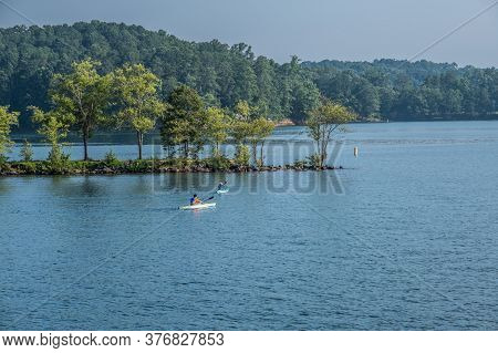 A Couple Kayaking Together On The Calm Lake Paddling Towards The Shoreline Of The Peninsula With The