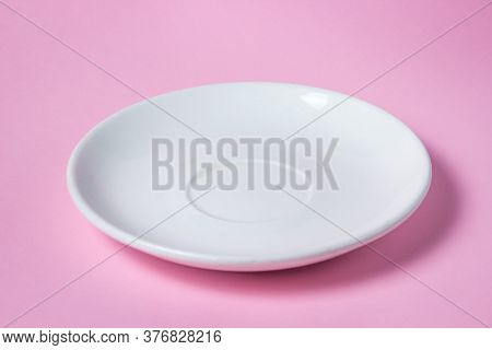 White Saucer On A Pink Background. Empty White Porcelain Saucer Stands On A Pink Surface