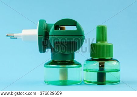 Green Fumigator On A Blue Background Close-up. A Spare Bottle Of Liquid Next To The Fumigator.