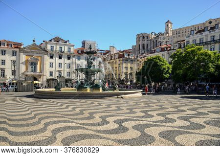 Rossio Square (or Pedro Iv Square) With Fountain, Typical Portuguese Cobblestone Hand-made Mosaic Pa