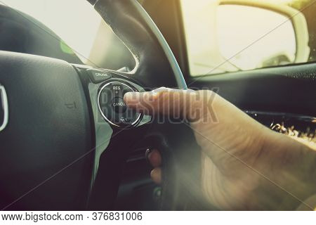 Driver Hand Pressing To Adaptive Cruise Control  Button On Steering Wheel Of A Car