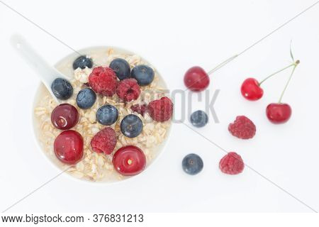 Rolled Oats With Blueberries, Raspberries And Sour Cherries On White Background. Healthy Breakfast C