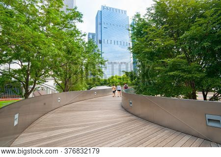 Chicago Usa - August 28 2015; Three People Walking Along Skating Ribbon Leading Between Greenery Of