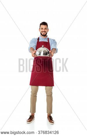 Handsome Waiter Smiling At Camera And Showing Metal Tray And Dish Cover On White Background