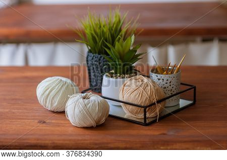 Balls Of Yarn In Neutral Beige Tones With Crochet Hooks On A Wooden Table, On A Light Background. Cr