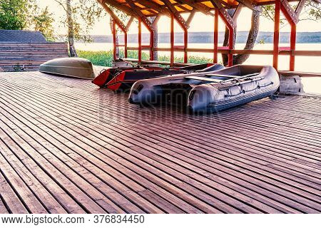 Under The Roof Are Two Inflatable Fishing Boats And One Plastic Pleasure Boat. Boat Drying Shed In A