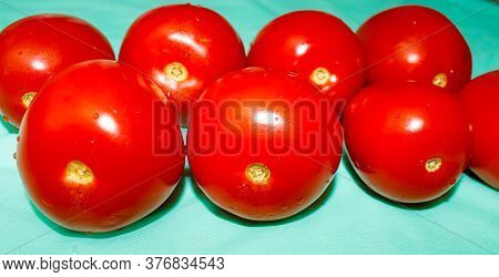 Several Ripe Red Tomatoes Lie In Two Rows On A Blue Background.