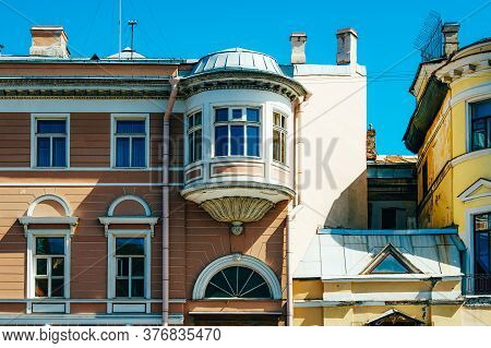 Classic Vintage Historical Building Bright Yellow Facade With Windows, Attic And Green Roof. Travel