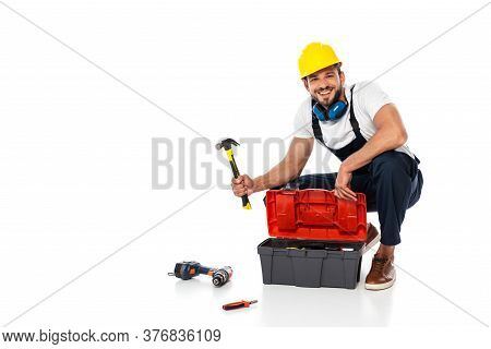 Smiling Workman In Uniform Holding Hammer Near Toolbox And Tools On White Background