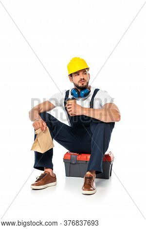 Handsome Workman Holding Coffee To Go And Paper Bag While Sitting On Toolbox On White Background
