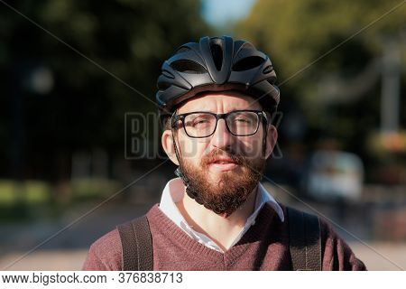 Portrait Of A Millennial Commuter In A Bicycle Helmet. Safe Cycling In The City, Going To Work On A