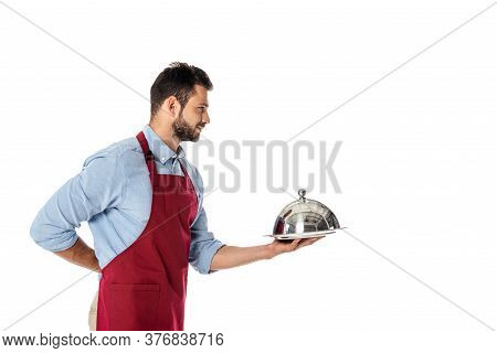 Handsome Waiter In Apron Holding Tray And Metal Dish Cover Isolated On White