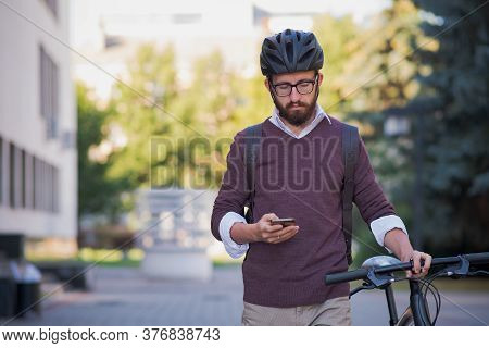 Millennial Bike Commuter In Helmet Walks With A Phone. Safe Cycling In The City, Green Transport, Us