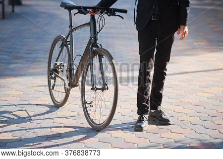 Male Person In A Suit Holding A Commuter Bike. Cycling Around The City, Going To Work By Bicycle