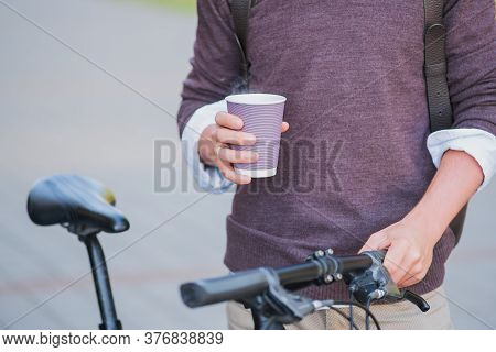Cup Of Hot Coffee In Hands Of A Bicycle Commuter. Going To Work By Bike, Active Urban Lifestyle Conc