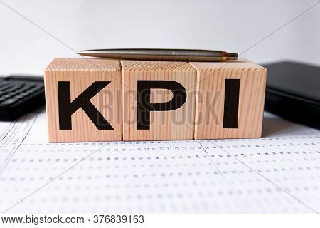 Kpi Word Written In Wooden Cubes, Key Performance Indicator. Financial, Marketing And Business Conce