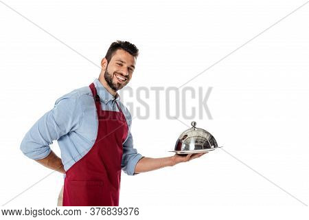 Waiter In Apron Holding Metal Dish Cover And Tray While Smiling At Camera Isolated On White