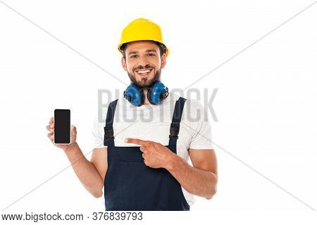 Smiling Workman In Uniform And Protective Helmet Pointing With Finger At Smartphone Isolated On Whit