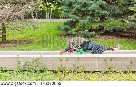 Chicago Usa - August 29 2015; Rough Sleeping Person Wrapped In Old Rugs Asleep On Concrete Beams In