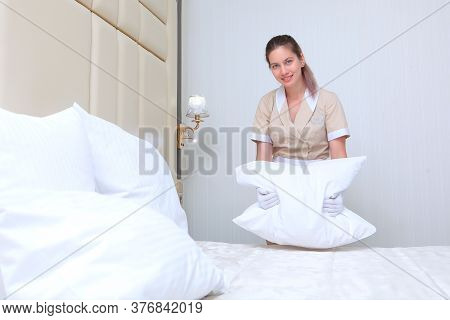 A Uniformed Maid Changes The Bed Linen In The Bedroom. The Concept Of Cleaning. Copy Of The Space. P