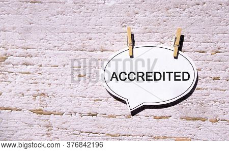 Accredited On A White Sheet With Wooden Pins