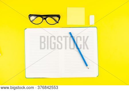 Black Eye Glasses, Erase Rubber, Pencil, Notepad Planner And Notepad Stick On Yellow Background. Fla