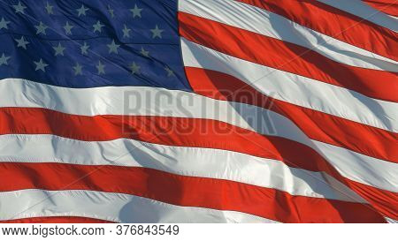 American Flag Waving. American Flag Blowing In The Wind With A Blue Sky Background. Close Up Of The