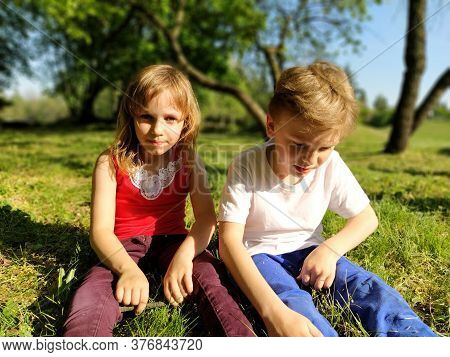 Two Children Are Sitting In A Meadow And Bored With Idleness. A Girl Of 6 Years Old And A Boy Of 7 Y
