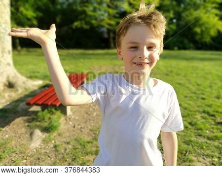 A White Boy Of 7 Years Old With Blond Hair And Gray Eyes Raises His Right Hand And Smiles. Child In