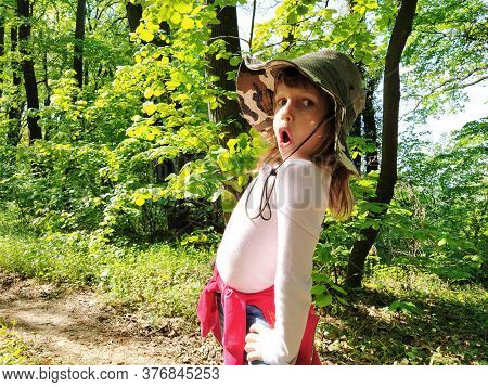 Beautiful Girl 6 Years Old In A Hunting Hat Makes A Grimace On Her Face. Emotion Of Surprise, Fear,