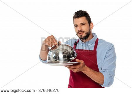 Handsome Waiter In Apron Holding Metal Tray And Dish Cover While Looking At Camera Isolated On White