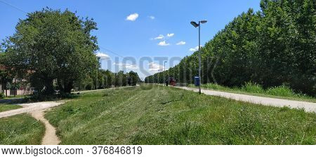 Sremska Mitrovica, Serbia, July 10, 2020. Mowing Grass By Tractor On The Embankment Of The Sava Rive