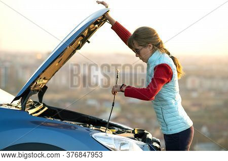 Young Woman Opening Bonnet Of Broken Down Car Having Trouble With Her Vehicle. Female Driver Near Au