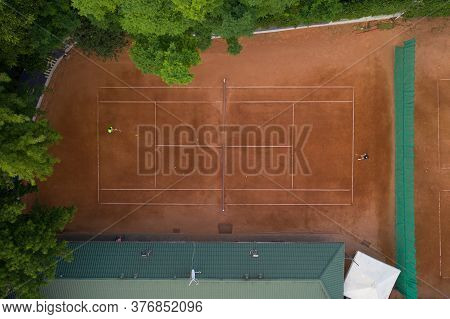Players Training On The Basis Of The Tennis Court. Aerial Shot. Tennis Clay Court With Players Who A