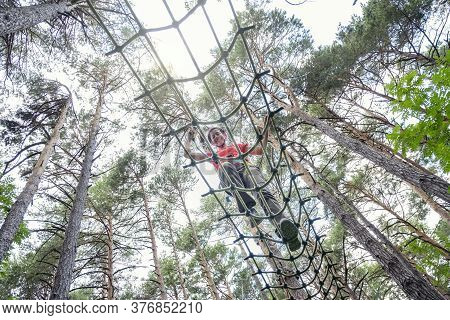 Woman Crossing A Tibetan Bridge In An Adventure Park In A Pine Forest View From Below