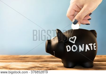 Hand Putting A Coin In A Black Piggy Bank With A Chalk Donate Tag On A Blue Background. Donation And