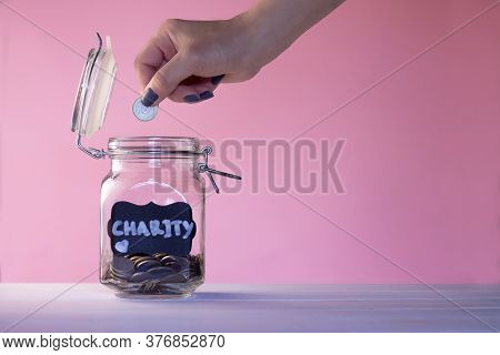 Hand Putting Coin In A Glass Jar With Coins With A Chalk Charity Tag On A Pink Background. Donation